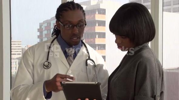 Doctor discussing results with patient on tablet / ipad
