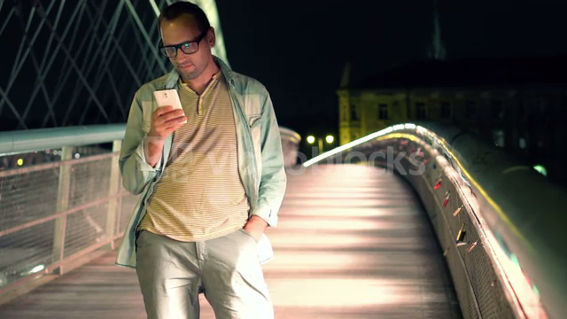 Young man texting on smartphone on the bridge in the city at night