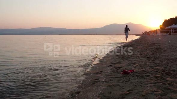 Man running away from the camera along a beach at the edge of the sea towards a glowing sunset as the sun dips below the horizon