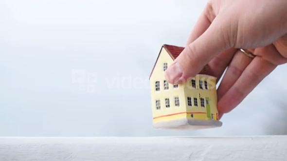 Hand putting a small toy house on the table on light background. Real estate or mortgage symbol