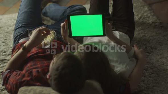 Young Couple are Laying on the floor and Watching Tablet PC with Green Screen at Home at Evening Time. Casual Lifestyle.