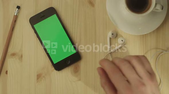 Phone with Green Screen Laying on a Wooden Table.