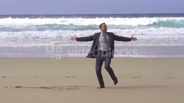 Happy businessman dancing on the beach, slow motion shot at 60fps
