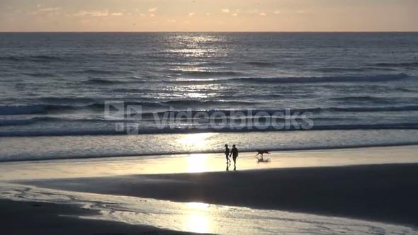 Couple and Dog Walking on Cannon Beach in Oregon