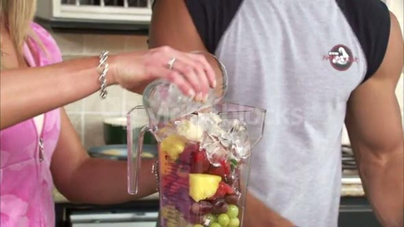 Couple Putting Fruit into a Blender 2
