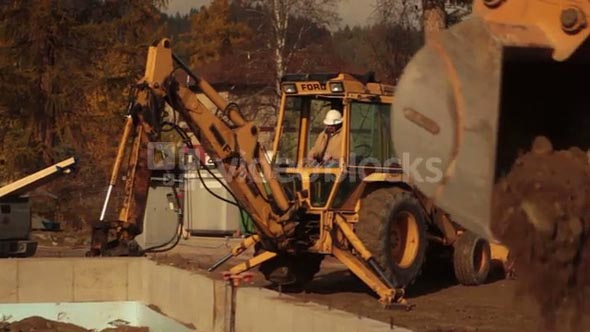 Construction Worker Operates Backhoe