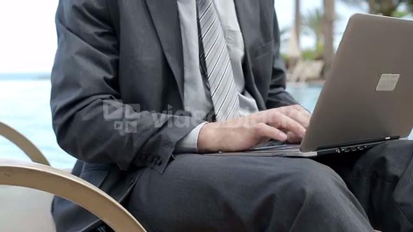 Closeup of businessman typing on laptop computer, steadycam shot