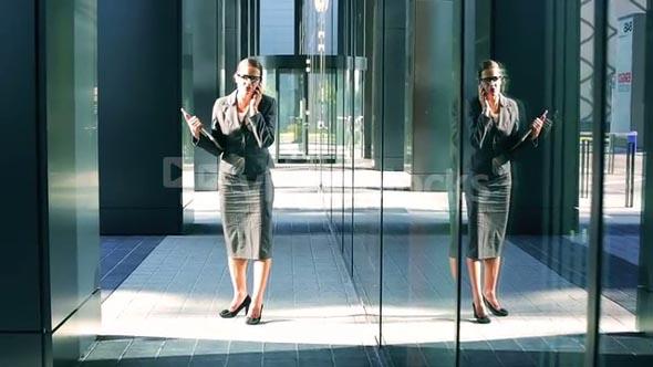 Businesswoman talking on cellphone walking