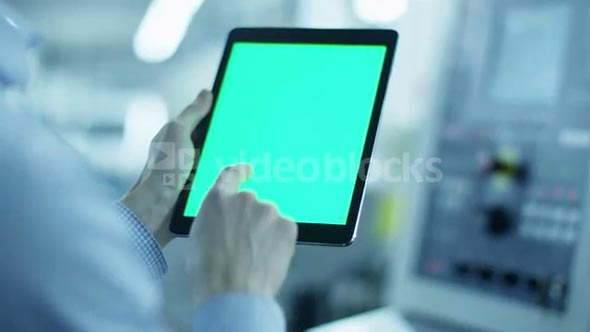 Worker is Using Tablet PC with Green Screen in Portrait Mode in Factory. Great For Mock-Up Usage.