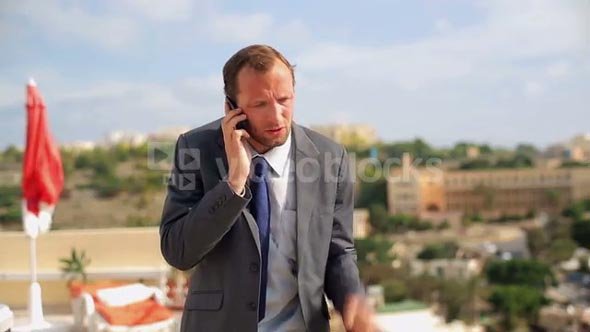 Angry businessman with cellphone standing on the terrace
