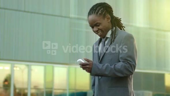 Steadicam shot of African American business man texting on his mobile phone in a modern city at sunset.