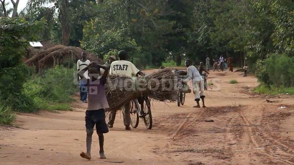 Rural Dirt Road In Africa With Children And Bicycles