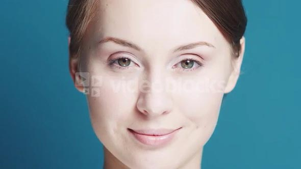 Closeup portrait of Beautiful healthy smiling woman with fresh skin. Slow Motion. Skincare concept. Young woman with glowing skin and bright eyes, beauty portrait on a blue keying background.