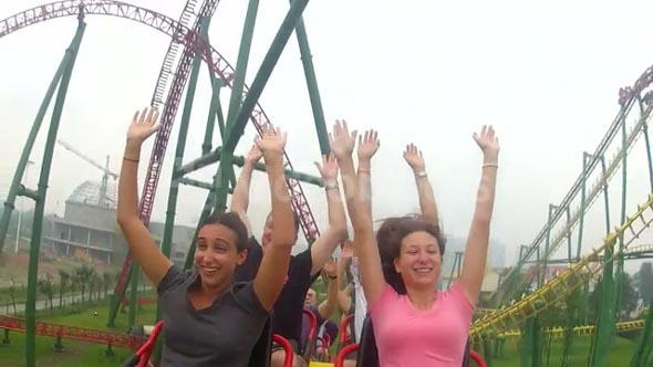 People Riding Coaster with Arms Up