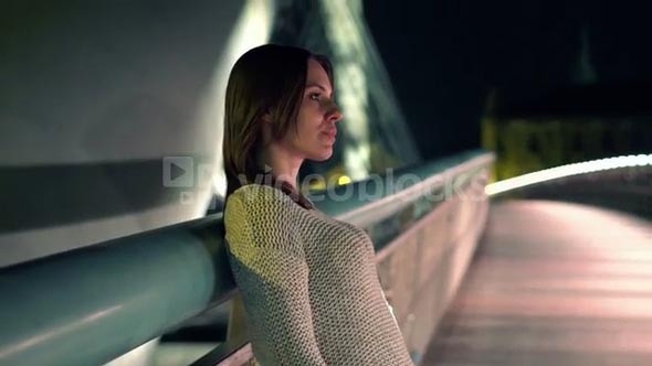 Young beautiful pensive woman standing on the bridge