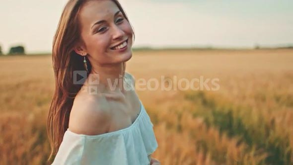 Beautiful girl running on sunlit wheat field