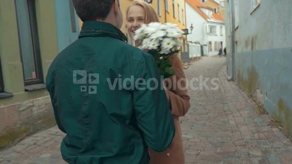 Slow motion of a happy girl running to her boyfriend and he meeting her with a bunch of flowers
