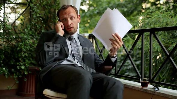 Angry businessman with cellphone after hard work on his balcony at home